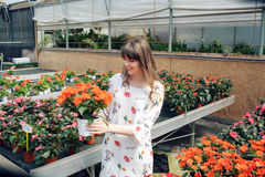 Young woman buying flowers at a garden center Stock Photo