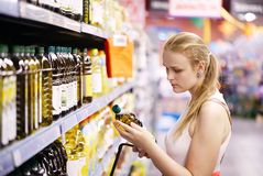 Young woman buying olive oil. Young blond woman picking an olive oil bottle from the shelves of a supermarket and reading the label Stock Photography