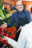 Young woman buying seasonal vegetables in grocery from mature se Royalty Free Stock Photography