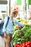 Young woman buying vegetables on market. Young pretty woman buying vegetables on market royalty free stock photo