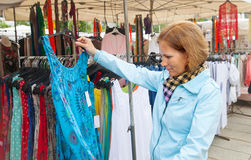 The young woman buys dress on market place Stock Images