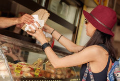 Young woman buys fresh pastries at bakery market Stock Photos