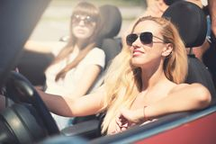 Young woman in cabriolet car departs for the summer holidays stock images