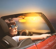 Young woman in cabriolet car near sea royalty free stock image