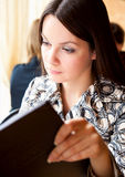Young woman in cafe. Young girl is reading menu in cafe Stock Photo