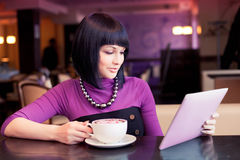 Young woman in cafe. Working with large coffee and computer tablet Stock Photo