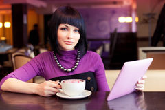 Young woman in cafe. Working with large coffee and computer tablet Royalty Free Stock Image