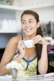 Young woman in cafe. Having coffe royalty free stock image