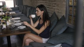 Young woman in a cafe, beautiful tourist brunette wait in restaurant stock video
