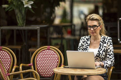 Young  woman at cafe with laptop looking at the camera Stock Photo