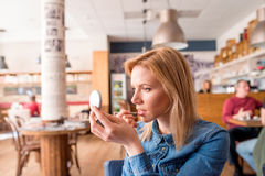 Young woman in cafe putting on lipstick looking into a mirror Royalty Free Stock Photo