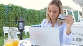Young woman at cafe using laptop and shopping online using credit card stock footage