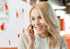 Young woman in Cafe. Very beautiful, happy,  young woman, sit in  Cafe and talk on telephone, horizontal closeup portrait Royalty Free Stock Image