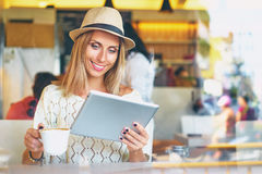 Young woman in cafe. Working at the cafe. Pretty young woman sitting at the table and using tablet computer indoor Royalty Free Stock Image