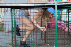 Young woman in cage. Long hair girl in cage Stock Photo