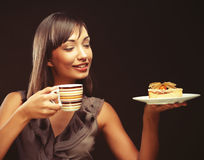 Young woman with a cake and coffee Stock Image