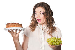 Young woman with cake and grapes isolated Royalty Free Stock Photography