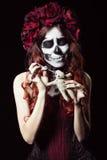 Young woman with calavera makeup (sugar skull) piercing voodoo doll Royalty Free Stock Image