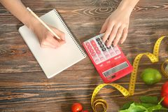 Young woman calculating calories at table. Weight loss concept Stock Photos