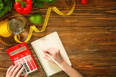 Young woman calculating calories at table. Weight loss concept Royalty Free Stock Photography