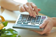 Young woman calculating calories at table. Weight loss concept Stock Photography