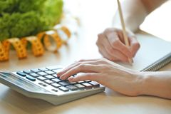 Young woman calculating calories at table. Weight loss concept Royalty Free Stock Photo