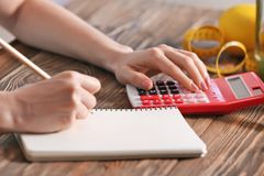 Young woman calculating calories at table. Weight loss concept Royalty Free Stock Photos
