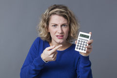 Young woman with calculator surprised by bad return on investment Royalty Free Stock Photos