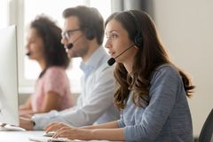 Young woman call center agent in headset consulting online client stock images