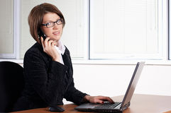 Young woman call with a phone. With laptop in office stock photography
