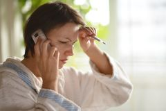 Young woman call. Young woman with a thermometer and a cold call the doctor Stock Photo