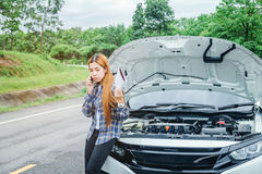 Young Woman calling for assistance with his car broken down by t Stock Image