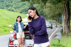 Young woman calling autoservice help with car problem. The young female traveler calling autoservice with broken down car and her friend standing near red car Stock Photos