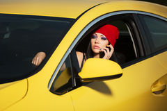 Young woman calling on cell phone in a car. Young woman calling on cell phone in the car Royalty Free Stock Photos