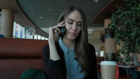 Young woman calling with cell telephone. Young attractive woman calling with cell telephone while sitting alone in coffee shop during free time, attractive stock video