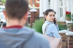 Young Woman Calling For Help On Mobile Phone Whilst Being Stalke. Woman Calling For Help On Mobile Phone Whilst Being Stalked On City Street By Man royalty free stock image