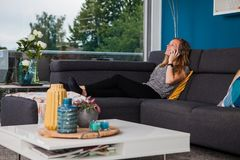 Young woman calling and laughing loudly on the couch stock images