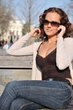 Young woman calling with mobile. Young smiling woman with sun glasses sitting on berm calling with mobile phone with street Stock Photo