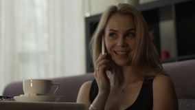 Young woman calling by mobile phone on background coffee cup at table in cafe. Close up beautiful woman talking by smartphone during coffee break in modern stock footage