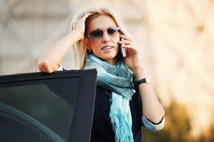 Fashion business woman in sunglasses calling on cell phone by car Royalty Free Stock Image