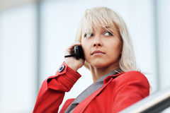Young woman calling on the phone against office wi Royalty Free Stock Images