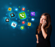 Young woman calling by phone with various icons. Attractive young woman calling by phone with various icons Stock Photo