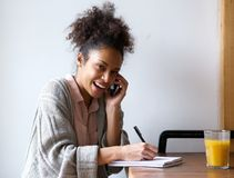 Young woman calling by phone and writing in notebook Stock Image