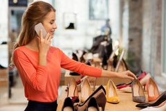 Young woman calling on smartphone at shoe store Royalty Free Stock Photos