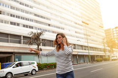 Young woman calling a taxi on city avenue Stock Photos