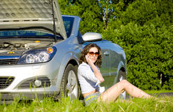 Young woman is calling to service near broken car royalty free stock image