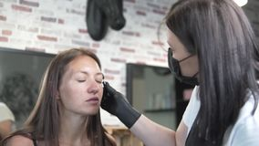 A young woman came to the beauty salon for coloring and eyebrow correction. Browser master brushes eyebrows with a brush before the procedure stock video