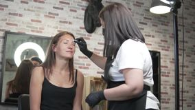A young woman came to the beauty salon for colors and eyebrow correction. A young woman came to the beauty salon for coloring and eyebrow correction. Browser stock video footage