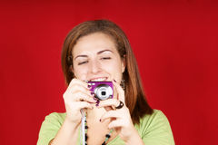 Young woman with camera. Portrait of a beautiful young woman taking a picture with a digital camera. Studio shot over red background. Shallow DOF. Horizontal Royalty Free Stock Photos