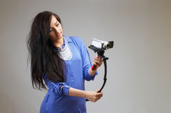 Young woman with camera. Young happy woman holding small video camera.at white background Stock Photography
